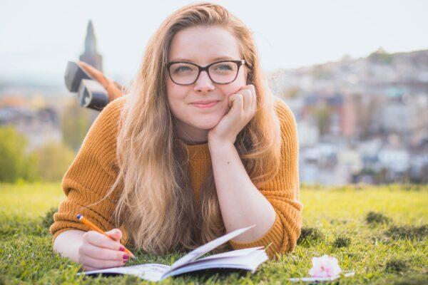 Flicka ligger på mage i gräs och studerar.